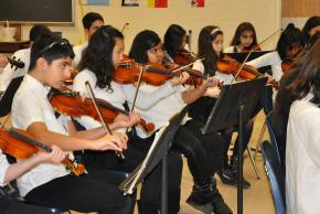 A picture of students playing stringed instruments