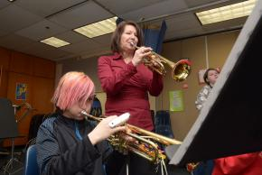 A picture of a band student playing a trumpet with the band director